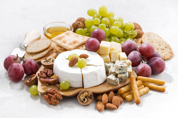 camembert, grapes and snacks on a white background, closeup