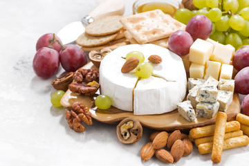 camembert, grapes and snacks on a white table, closeup