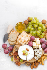camembert, grapes and snacks on a white table, vertical