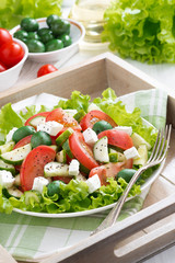 plate of green salad with vegetables and feta, vertical