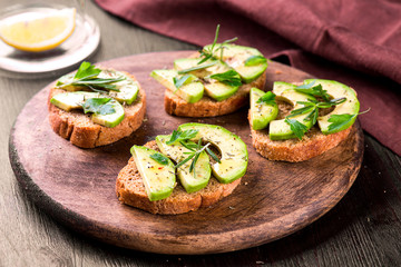 Toast with avocado, herbs on wooden board