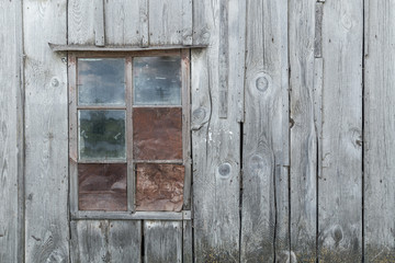 Natural lit vintage, old window in an ancient wooden weatherd grey wall in an abandoned farm barn, with room for copy space