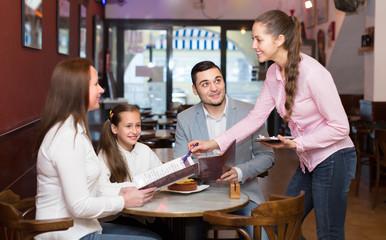Waitress serving family of three