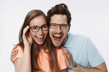 Couple in eyeglasses smiling at camera