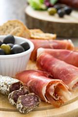 Spanish serrano ham, olives and sausages on wood