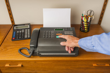A hand pushing start button on an old retro style fax machine