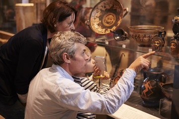 Family Looking At Artifacts In Glass Case On Trip To Museum