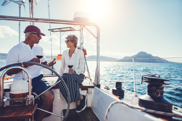 Mature couple talking and enjoying red wine on yacht