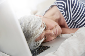 Exhausted woman sleeping on laptop