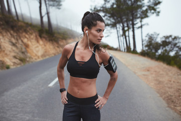 Confident young female athlete standing on country road
