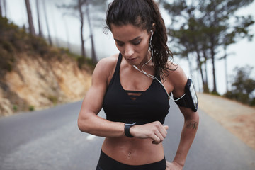 Young sporty woman checking smart watch outdoors