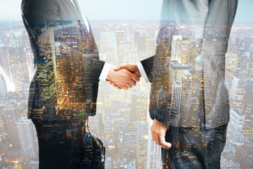 Businessmen shaking hands city background