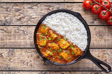 Tikka masala traditional butter chicken spicy meat food and rice with tomatoes in cast iron skillet on vintage wooden background. Karahi chicken recipe