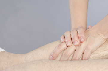 Closeup of hands of chiropractor doing calf muscle massage to ma