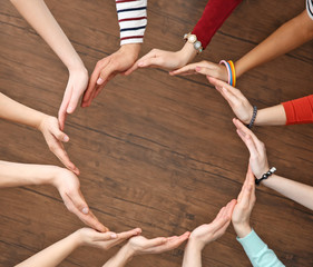 Group of people hands together on wooden background