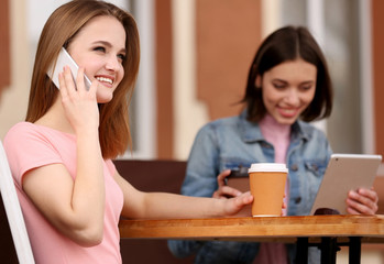 Young happy women drinking coffee and talking in cafe