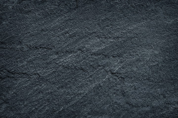 Dark grey / black slate stone background or texture.