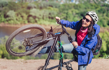 Young woman biker traveler hold her bike up happy smiling outdoor. Cross country female biker relaxing and joking after riding a bike