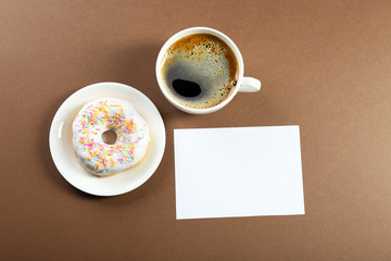 Cup of fresh coffee and note on brown background