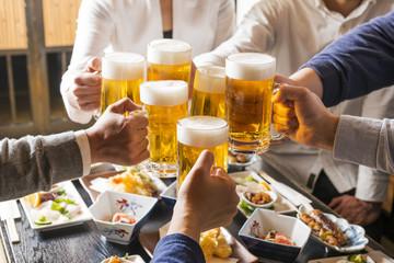 居酒屋で乾杯をする男女