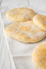 Pita on a napkin at the edge of the table