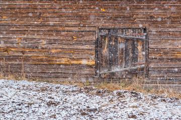 Snowfall and old wooden barn wall