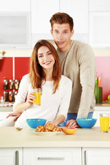 Couple having breakfast in kitchen