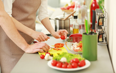 Loving couple cooking salad in kitchen