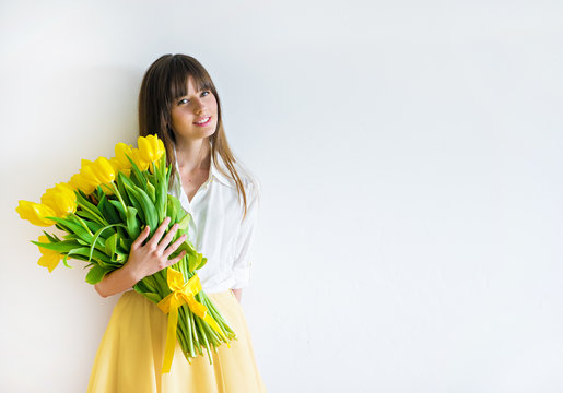 young happy woman with yellow tulips