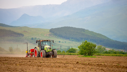 Fototapete - Tractor plows a field in the spring.