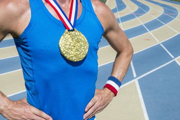 American athlete standing with gold medal and USA colors red, white, and blue ribbons at a blue and tan running track