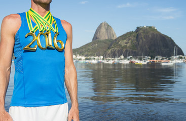 First place Brazilian athlete wearing gold 2016 medals standing outdoors in front of a view of Sugarloaf Mountain and Guanabara Bay from Botafogo Beach, Rio de Janeiro, Brazil