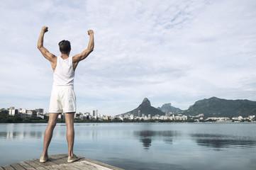 Athlete in white sport uniform standing in front of Rio de Janeiro Brazil skyline at Lagoa Rodrigo de Freitas lagoon