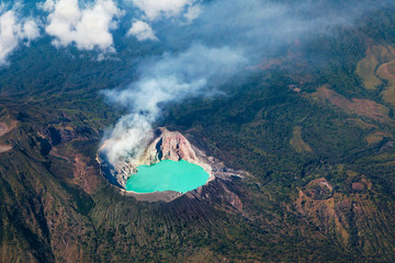 Aerial photo of active volcano Ijen in East Java - largest highly acidic crater lake in world with turquoise sulphuric water. Place of sulfur mining. Famous travel destinations of Indonesian islands.