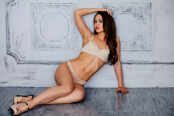 Sexy girl in underwear sits on the floor in the Studio.