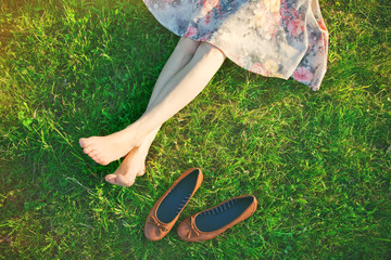 girls legs lying in grass barefoot without shoes