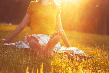 girl sitting in grass barefoot without shoes in summer sun