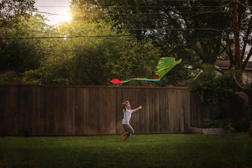 Boy in garden flying kite