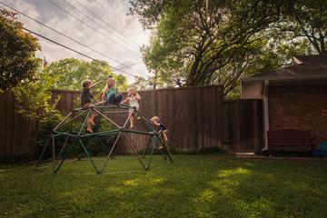 Children in garden climbing on climbing frame