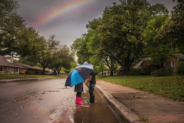 Boy and girl in puddle under umbrella and rainbow