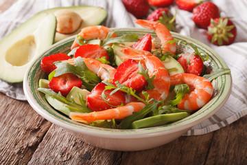 Fresh salad with strawberries, avocado, shrimp and arugula close-up. horizontal