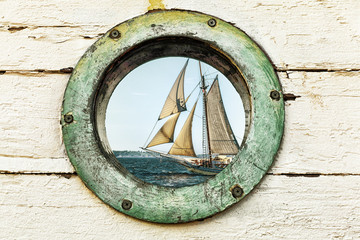Old porthole window looks out at an old sailing ship. Vintage color