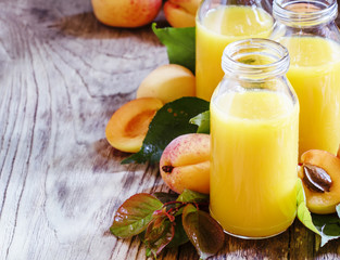 Freshly squeezed apricot juice in glass bottles, fresh fruit wit
