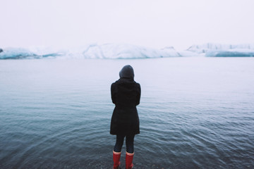Woman in front of lake looking at icebergs