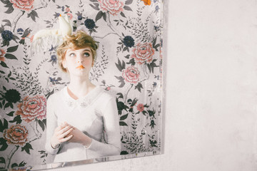 Mirror image of woman in front of floral wallpaper with bird hair ornament