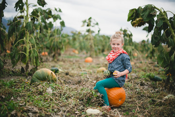 Girl sitting on pumpkin in field, portrait