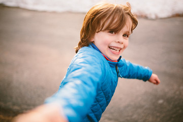 Young boy running outdoors