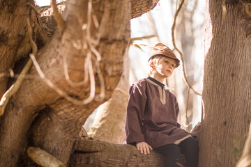 Young boy sitting in tree, wearing hat with feather