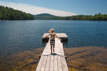 Young boy walking along jetty on lake, rear view