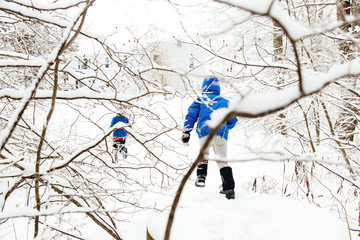 Two young boys playing in snow in rural landscape